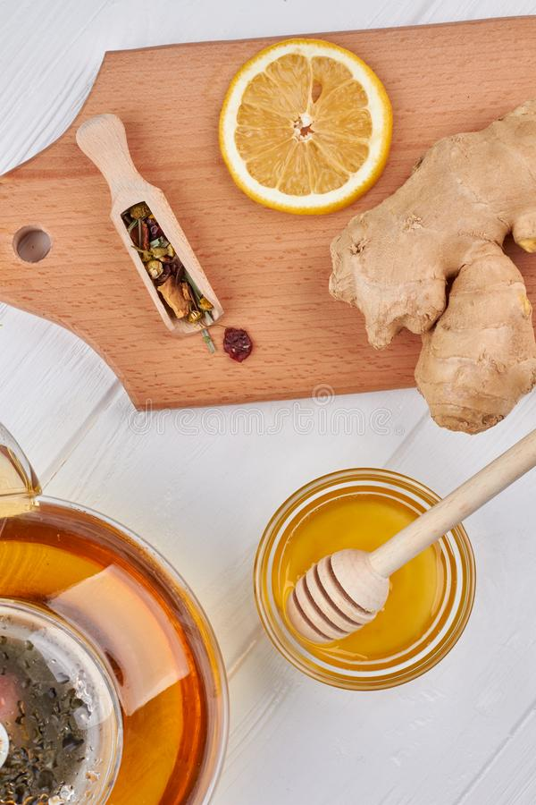 Teapot, honey, ginger and slice of lemon. Ingredients for healthy beverage. Treatment of flu stock photography