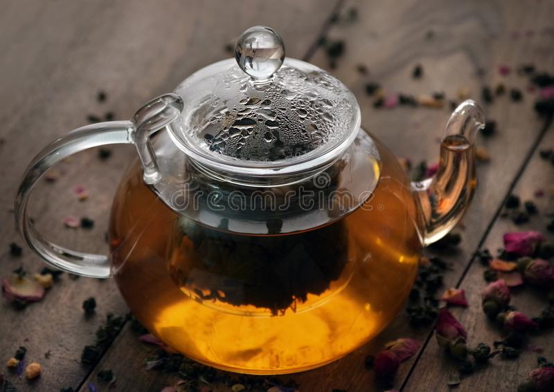 Teapot with hot tea. fresh brewed tea. tea and roses on a wooden table. stock photos