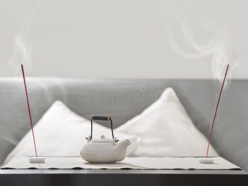 Teapot i kadzidła kij na stole zdjęcie stock