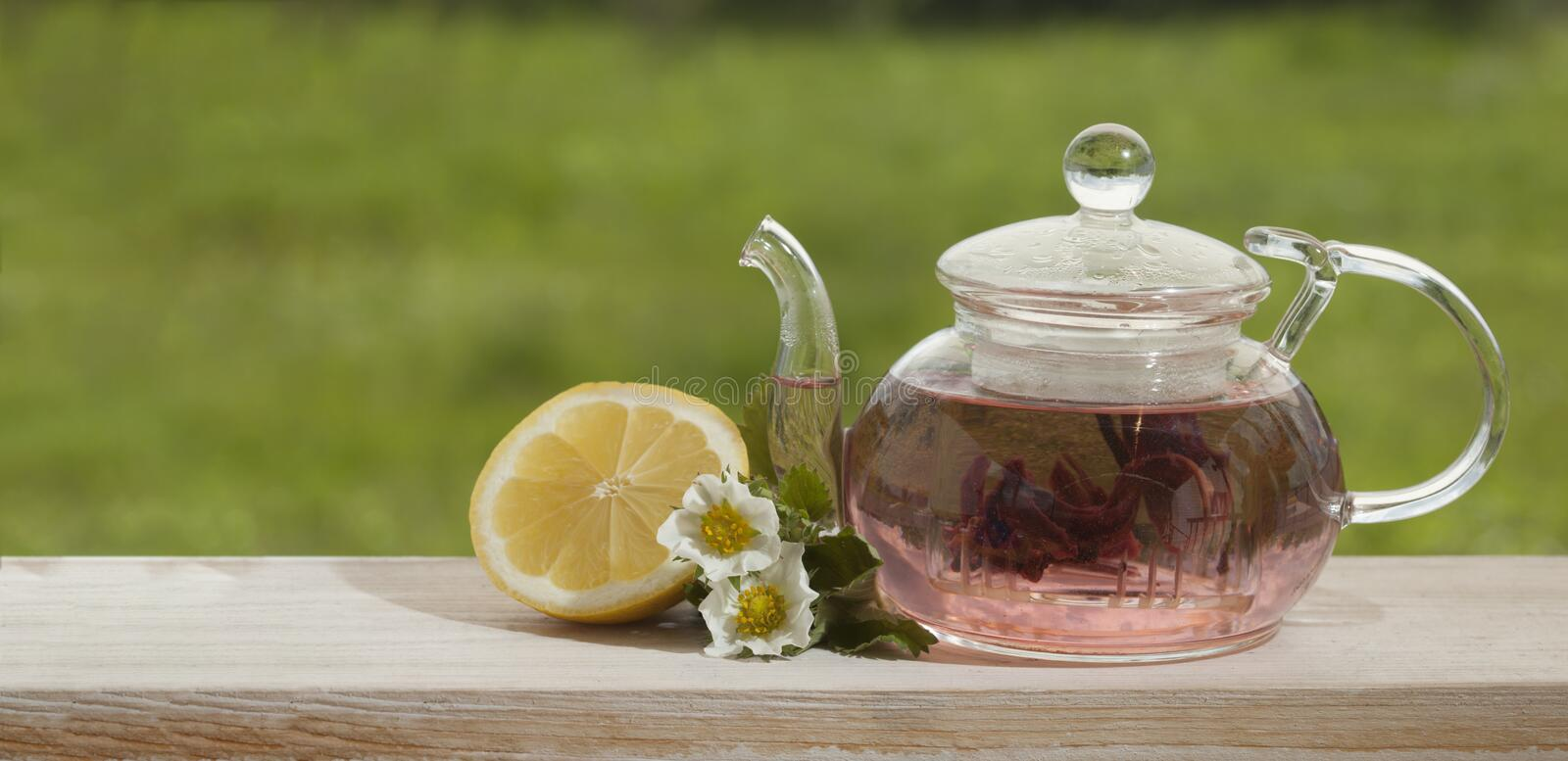 Download Teapot With Lemon Tea On A Background Of Nature Stock Photo - Image of carcade, breakfast: 113616906