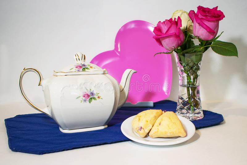 A teapot, pink heart, roses and scones stock photo