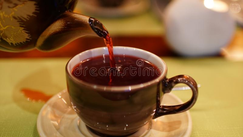Teapot pouring tea into a cup on surface. Teapot pouring tea into a brown ceramic cup on surface royalty free stock photography