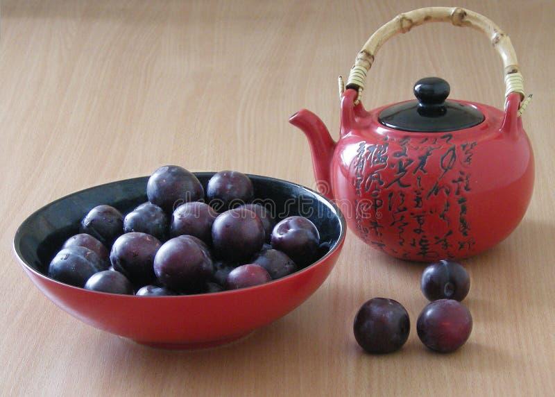 Teapot red вowl with plums stock photos