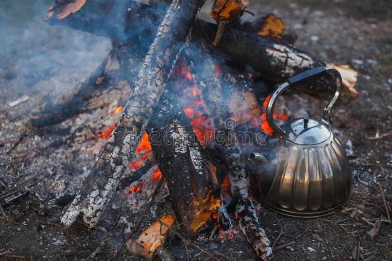 A teapot with tea stands by the fire. Evening photography royalty free stock photography