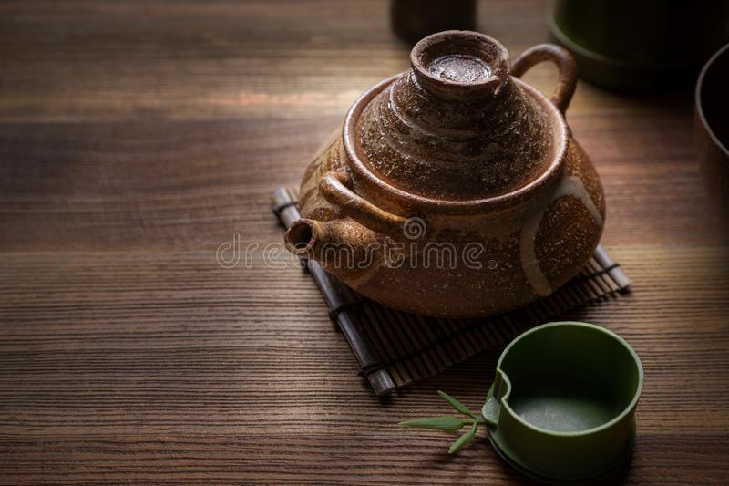 Teapot , teapot on a wooden table. Teapot and a cup of tea on an old wooden table - hot steam smoking from cup of tea royalty free stock image