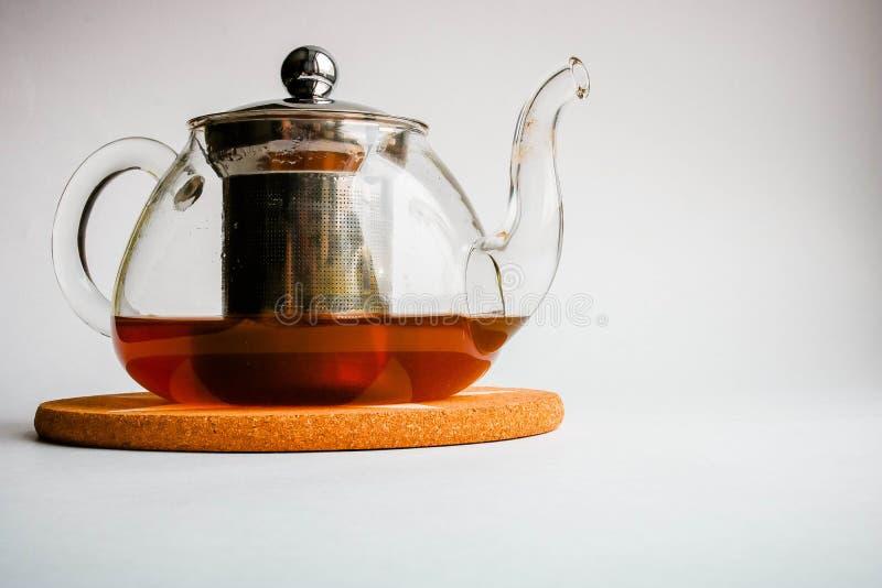 Teapot on white background. Fresh black tea royalty free stock photography