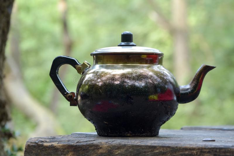 Teapot on wood fire at the camping site . old, dirty, iron kettle on the table royalty free stock image
