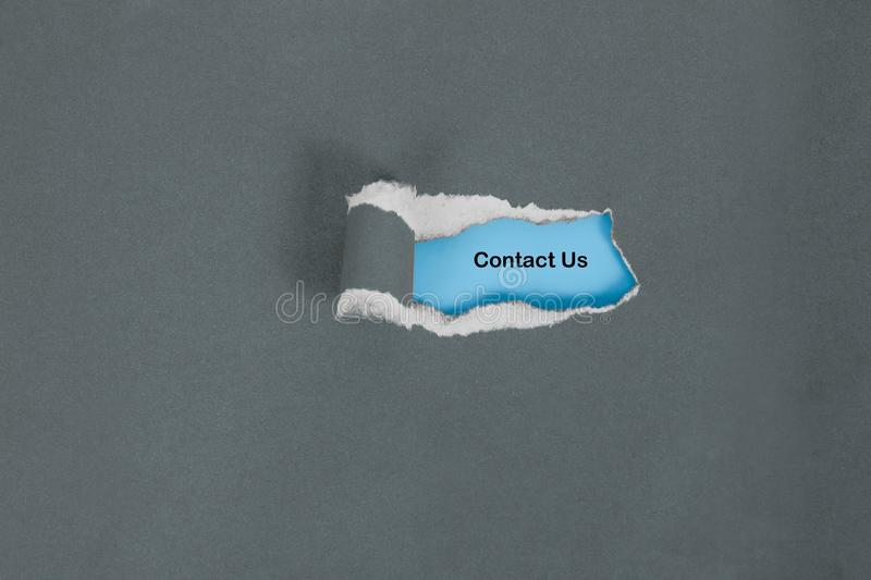 Tear color paper to see contact us text , business stock photos