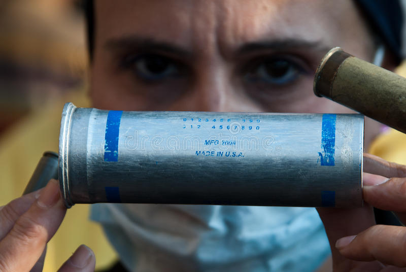 Tear gas cartridge. A woman shows the weapons used by police during fighting in main square of Cairo. In this case we can see an 37mm 150 yard range CS gas smoke royalty free stock photography
