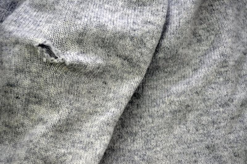 Tear in knit fabric, close up. Hole on the grey sweater. Texture of woolen fabric of an old sweater stock photography