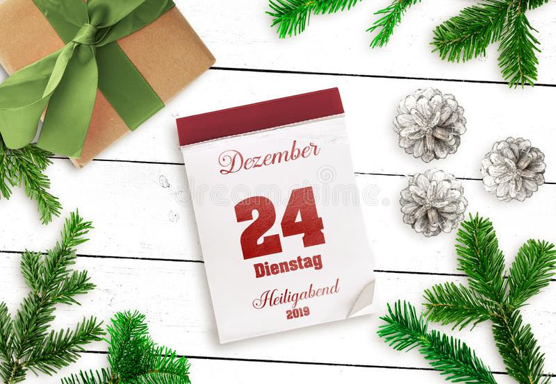 Tear-off calendar on December 24 Christmas Eve 2019 on white wooden table. Top view of tear-off calendar on December 24 Christmas Eve 2019, in German language royalty free stock image