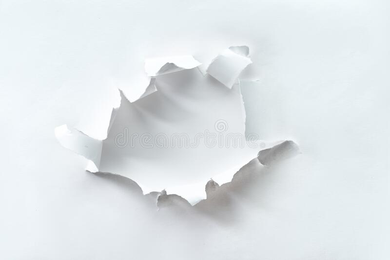 Teared paper hole in white paper over white background for your text or product. Flat lay, overhead angle, square composition. Ripped hole, abstract element royalty free stock images