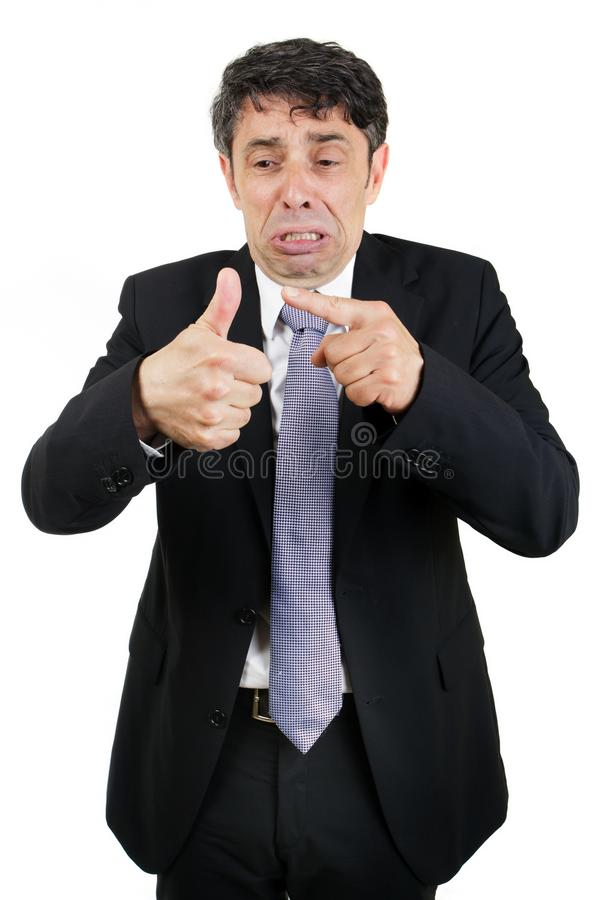 Tearful man pointing to his injured. Tearful business man pointing to his injured thumb with a woeful piteous expression isolated on white stock image