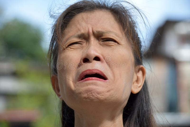Tearful Old Filipina Person. A pretty asian adult female stock photography