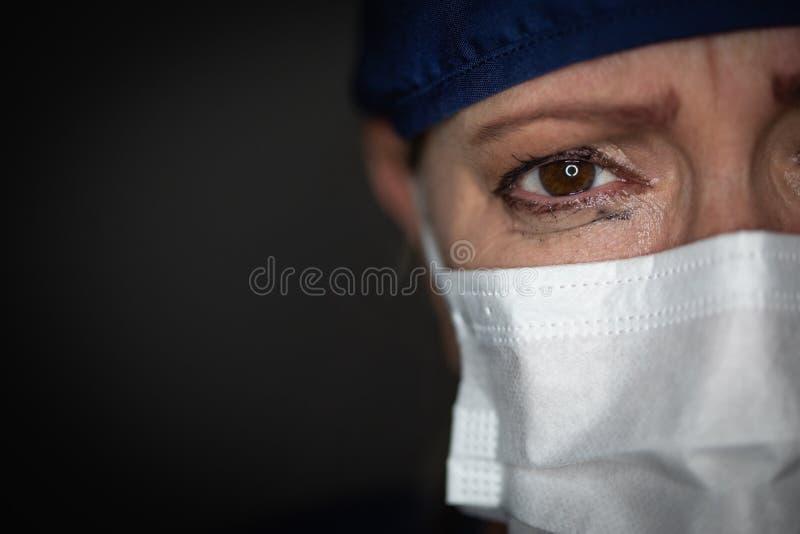 Tearful Stressed Female Doctor or Nurse Crying Wearing Medical Face Mask on Dark Background. Tearful Stressed Female Doctor or Nurse Wearing Medical Face Mask on stock image