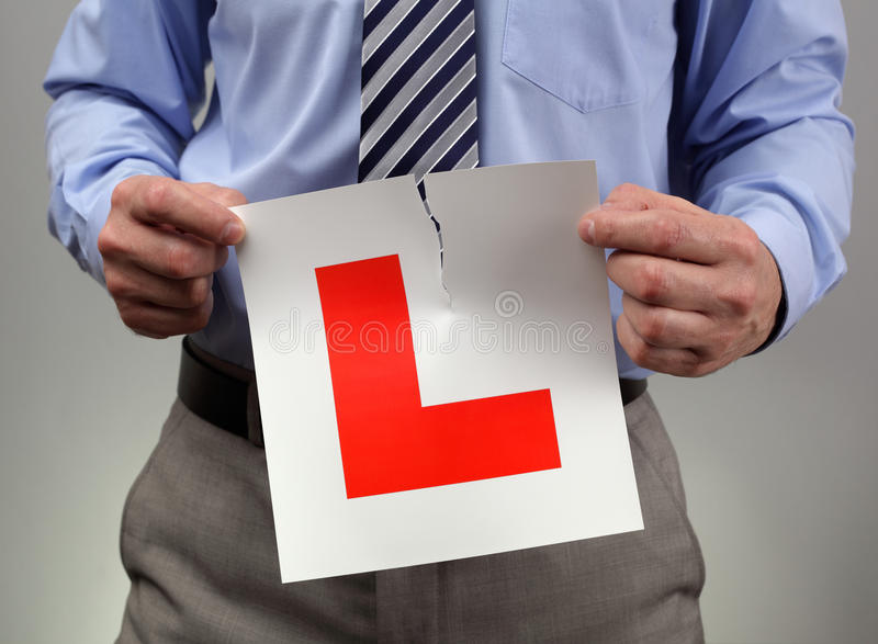Tearing up L plate. Businessman tearing up L plate concept for new business, apprenticeship or passing driving test stock photo