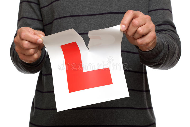 Tearing up L plate after passing driving test. Tearing L plate after passing driving test against white background concept for success stock photography