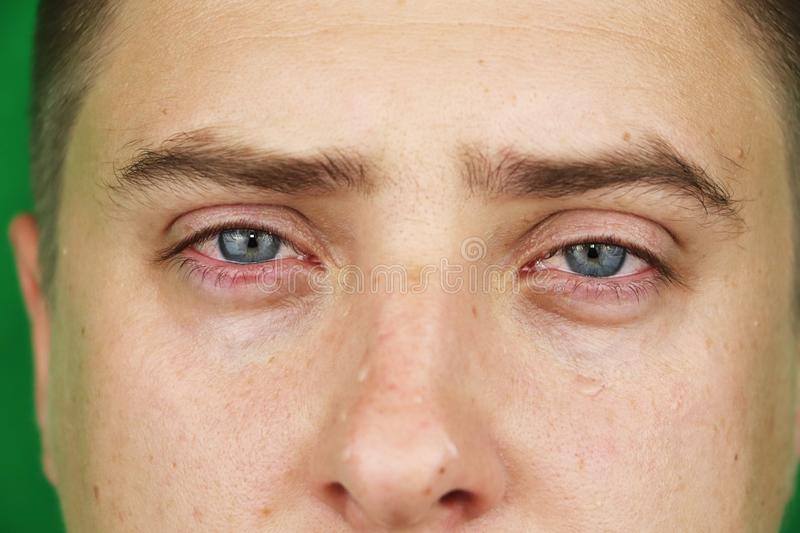 Tears in eyes of crying adult man. Green background. Chromakey stock images