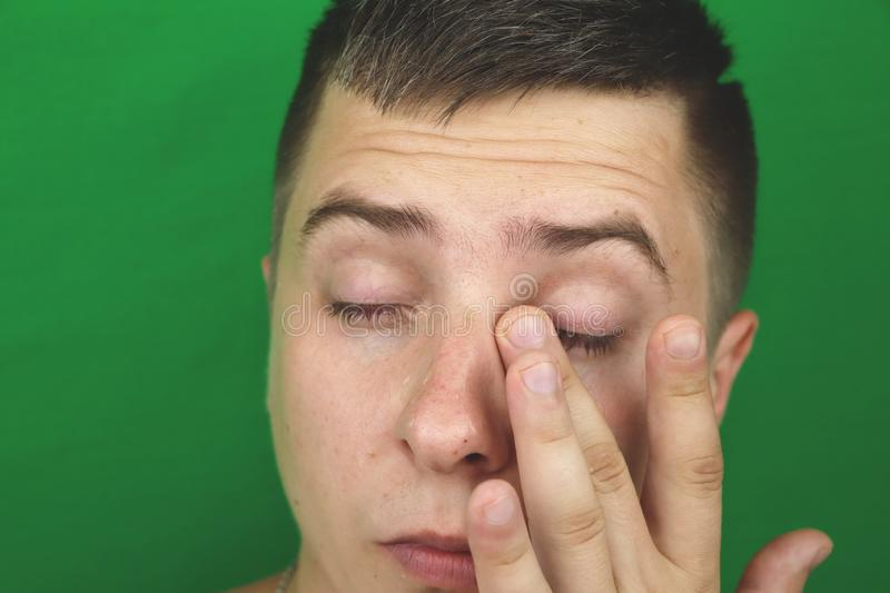 Tears in eyes of crying adult man. Green background. Chromakey royalty free stock photo