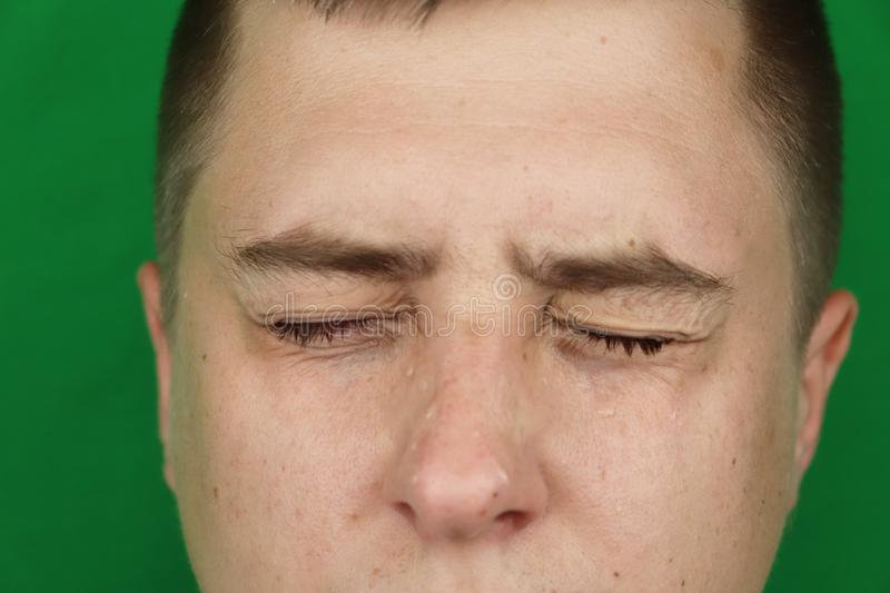 Tears in eyes of crying adult man. Green background. Chromakey royalty free stock image