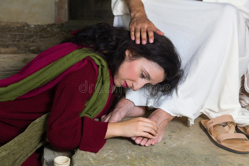 Tears of shame of Mary Magdalene. Mary Magdalene crying of shame and embalming Jesus` feet royalty free stock image