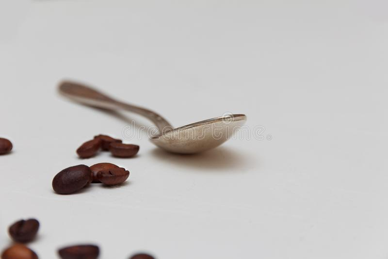 Teaspoon with coffee. A teaspoon on a light table with scattered coffee beans stock photo