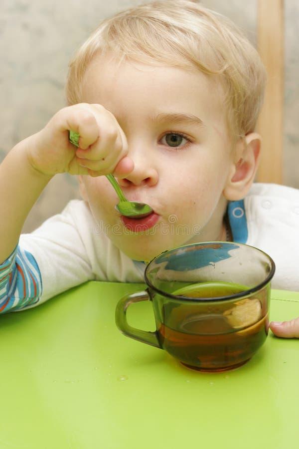 Teaspoon da terra arrendada da criança em sua boca fotos de stock