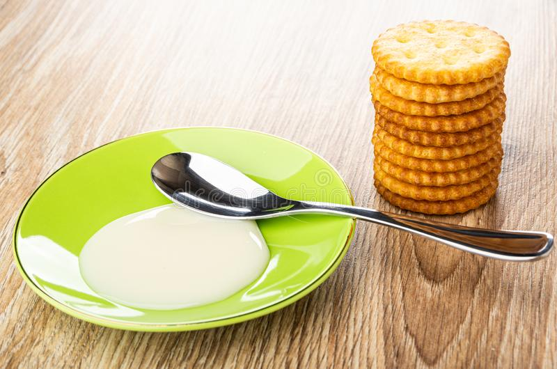 Spoon in saucer with condensed milk, stack of crackers on wooden table stock photo