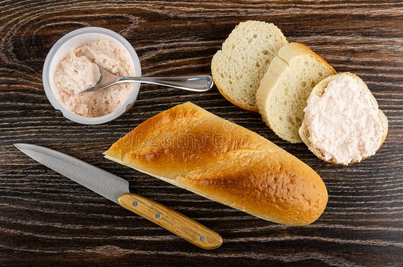 Spoon in jar with krill paste, knife, loaf of bread, bread, sandwich with krill paste on wooden table. Top view stock photography