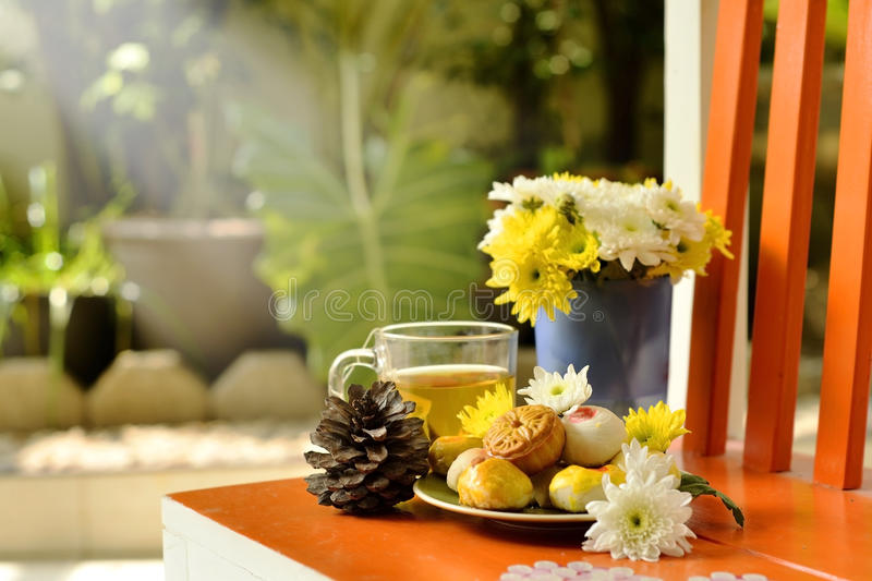 Teatime with Chinese pastry and tea and flower on a orange chair royalty free stock image