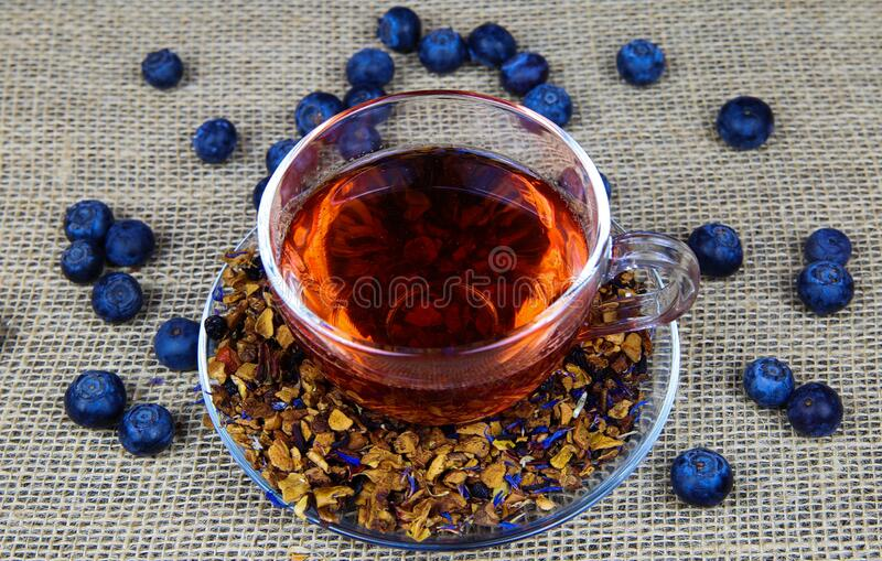 Teatime: Close up of transparent glass fruit tea cup on jute mat background.with fresh blue blueberries royalty free stock photography