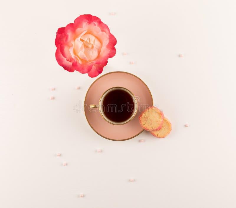 Teatime, taza rosada de té, rosa rosada y galletas de las galletas en la tabla blanca Visi?n superior Copie el espacio imagen de archivo libre de regalías