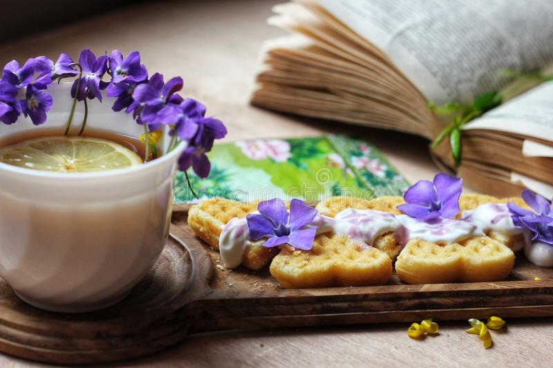 Teatime. Tea flowers booking book flatlay design lemon waffel blueflowers iris waffels goffres flatlay chillout oak wood woodworking learning stock photography