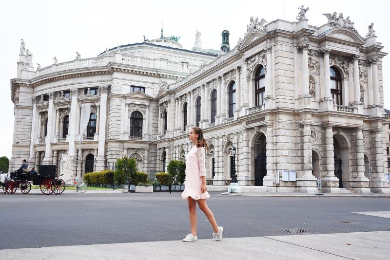 Teatro Burgtheater do estado de Viena, Áustria Uma menina em um vestido cor-de-rosa está no fundo da construção fotografia de stock