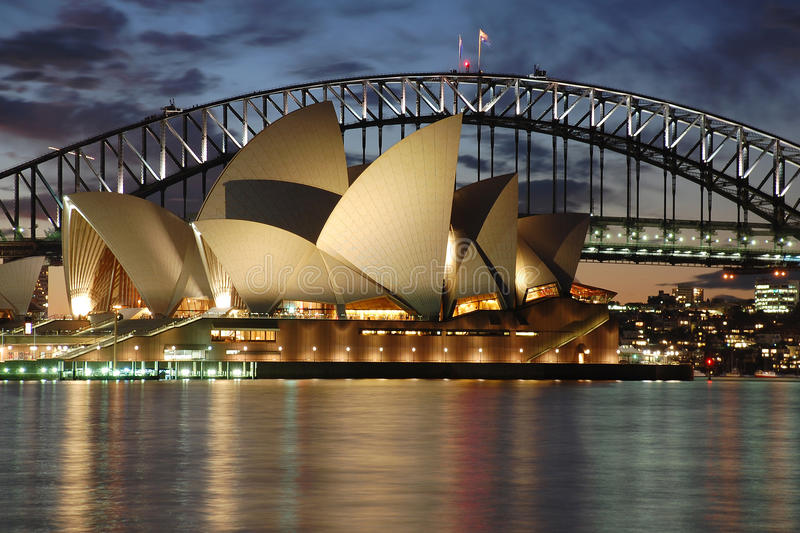 Teatro de la ópera de Sydney de la noche con el puente del puerto imagen de archivo
