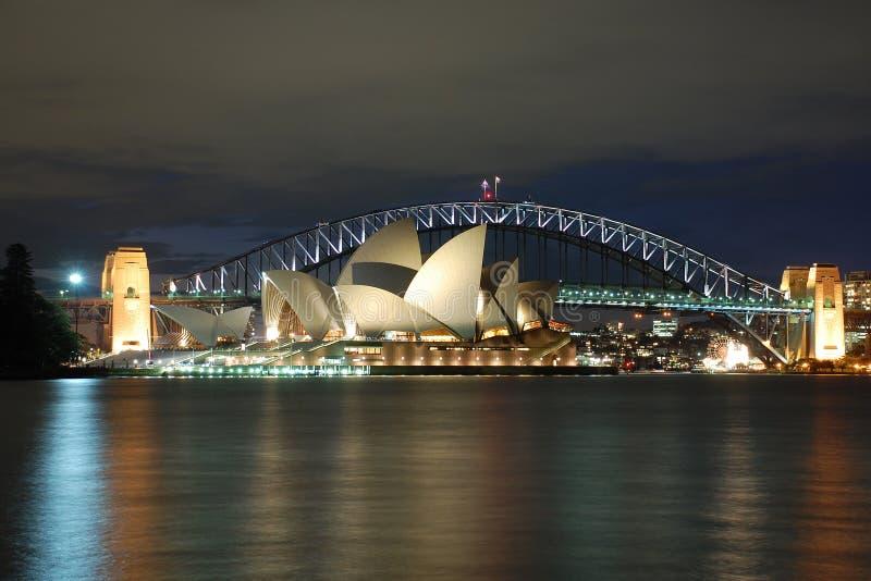 Teatro de la ópera de Sydney de la noche con el puente del puerto imagenes de archivo