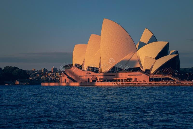 Teatro de la ópera durante la situación de la puesta del sol en orilla azul del océano y la línea del cielo en Sydney en un día d fotografía de archivo