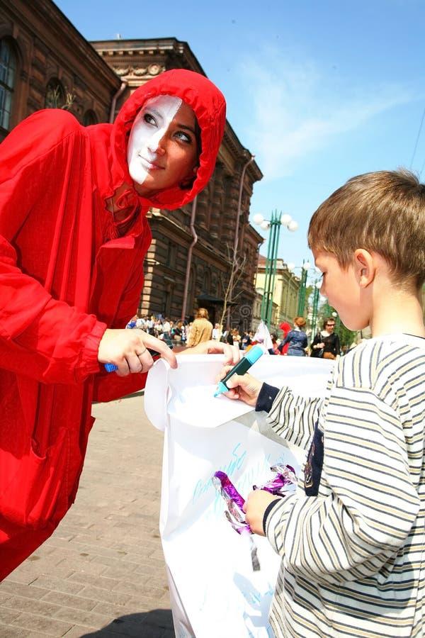 Teatro de la calle abra el funcionamiento vestido calle de actores jovenes Un niño drena imagen de archivo libre de regalías