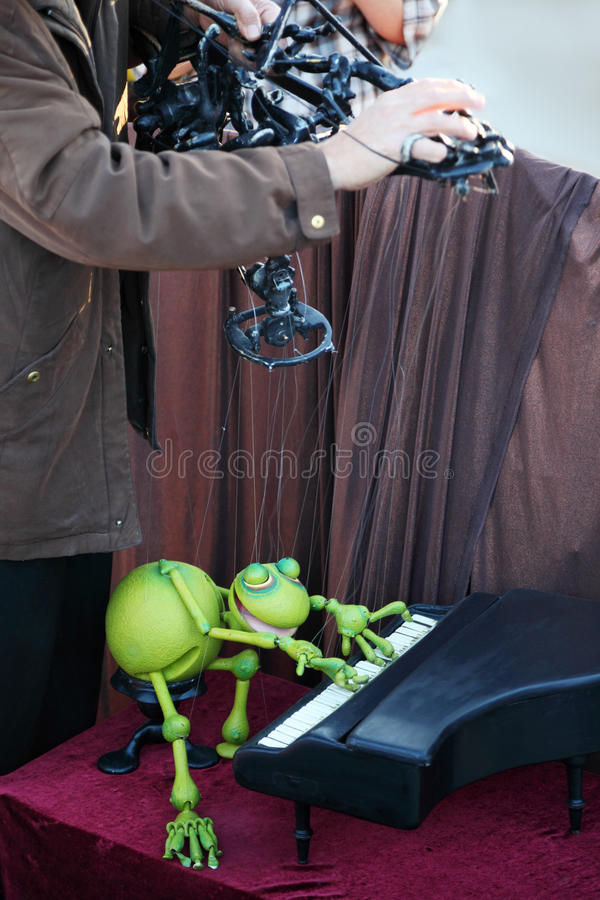Teatro de la calle - juegos de marioneta de la rana en pequeño piano fotografía de archivo