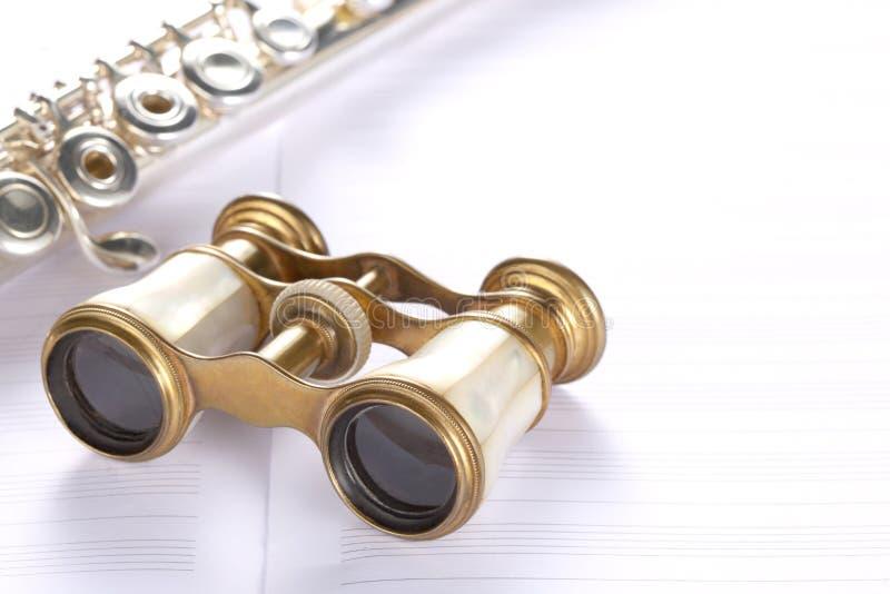 Teatro de los prismáticos y un resto de la flauta transversal en cuenta de la música imagen de archivo