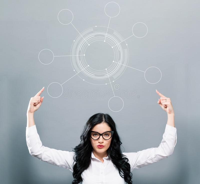 Tech circle with business woman pointing upwards. On a gray background royalty free stock image