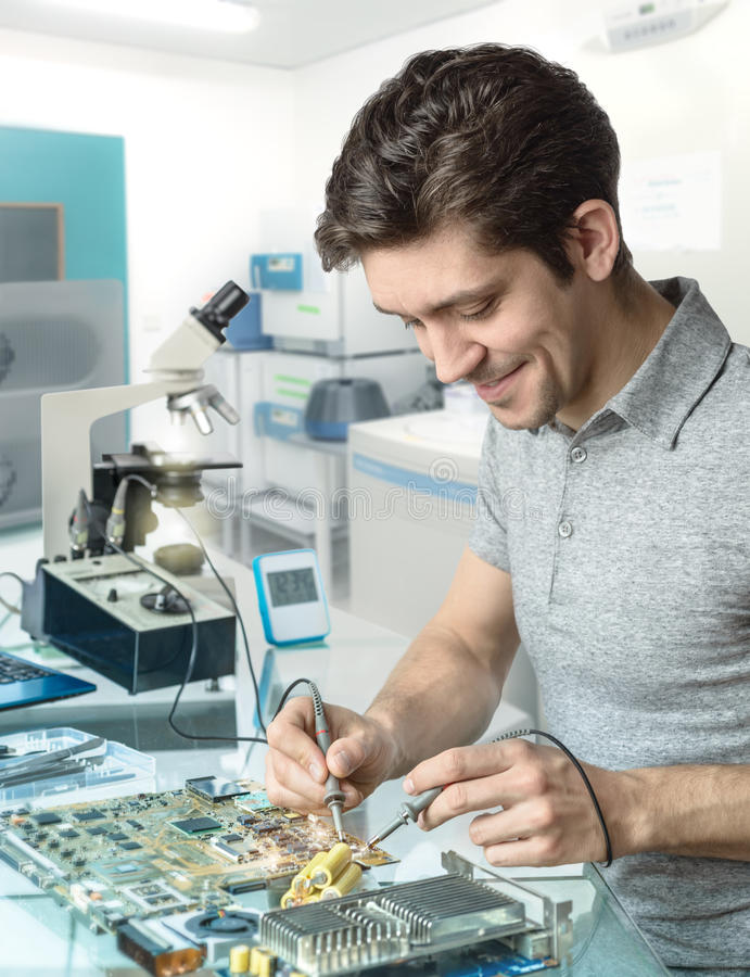 Tech or engineer repairs electronic equipment in research facility. Young energetic male tech or engineer repairs electronic equipment in research facility stock images
