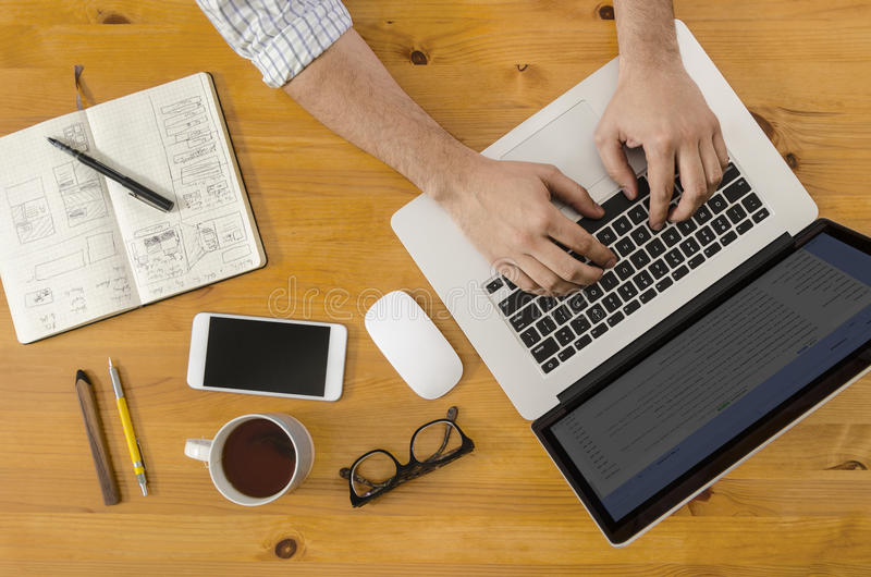 Tech Hipster Working at Wooden Desk on Laptop royalty free stock images