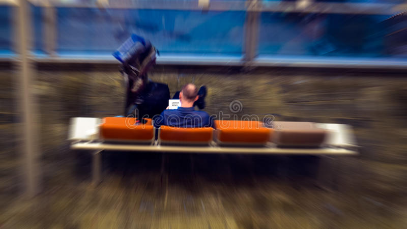 Tech on the Move - Man Surfing News on PC Tablet stock photography