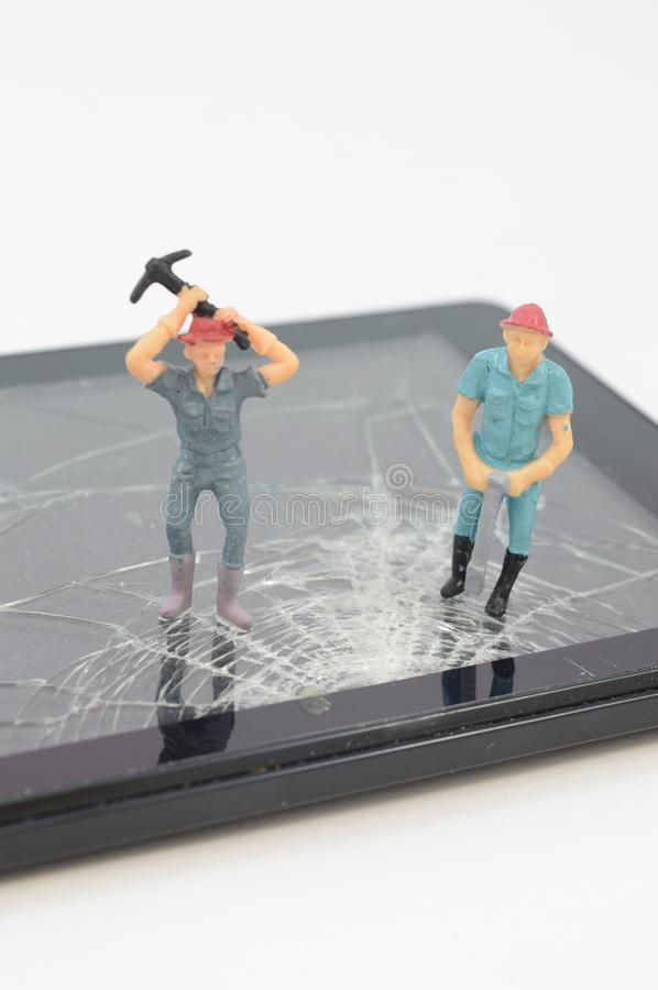 Tech Support Team. Are on the task of the broken touch screen device in need of repair, accident, achievement, cellphone, crack, cracked, damage, damaged royalty free stock photo