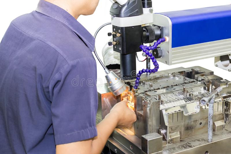Techncian during repair metal mold and die part by laser welding method on wihte background.  stock photography