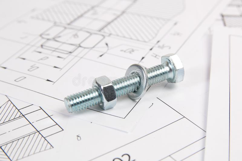 Technical drawings of bolt and nut. Engineering, technology and metalworking. Metal bolt and nut on printed drawings background royalty free stock photography