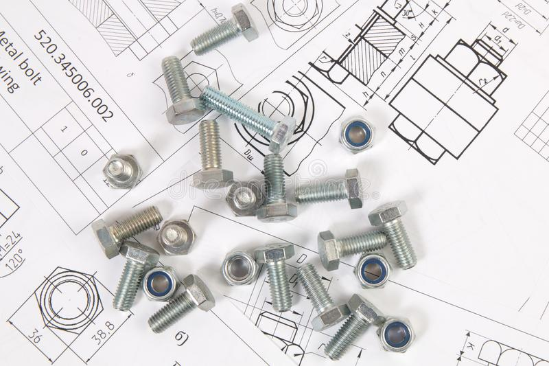 Technical drawings of bolt and nut. Engineering, technology and metalworking. Metal bolt and nut on printed drawings background stock photos