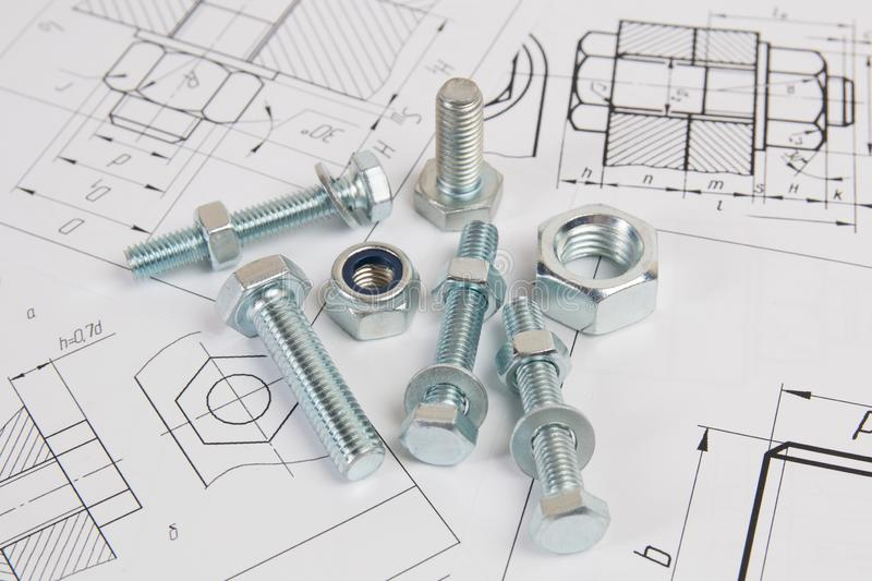 Technical drawings of bolt and nut. Engineering, technology and metalworking. Metal bolt and nut on printed drawings background stock images