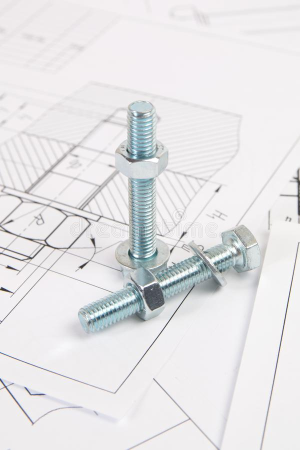 Technical drawings of bolt and nut. Engineering, technology and metalworking. Metal bolt and nut on printed drawings background stock photo